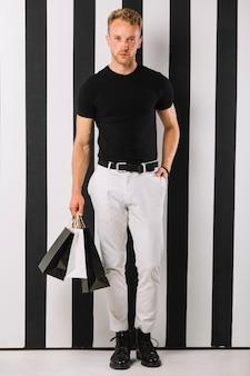 Hübscher erwachsener mann, der einkaufstaschen hält