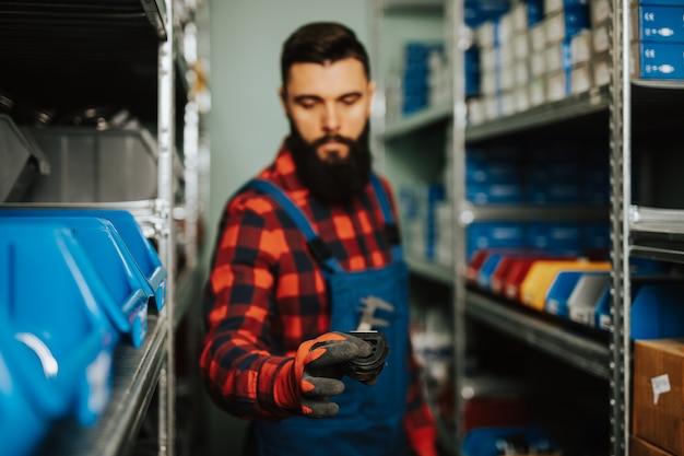 Hübscher erwachsener mann, der im ersatzteillager für pkw und lkw arbeitet. Premium Fotos