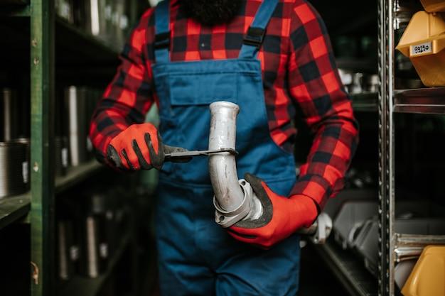 Hübscher erwachsener mann, der im ersatzteillager für pkw und lkw arbeitet.