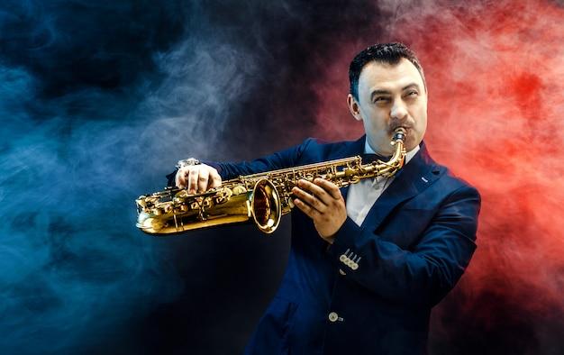 Hübscher erwachsener mann, der saxophon spielt