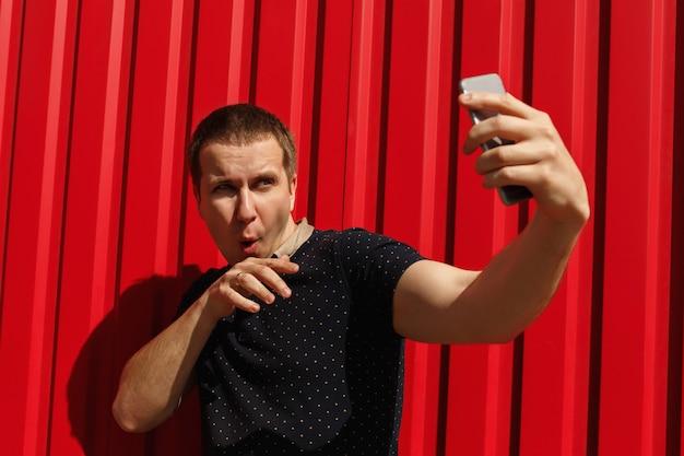 Hübscher erwachsener mann, der sein handy verwendet und auf rotem hintergrund mit freiem raum lächelt. glücklicher junger mann, der über rotem wandhintergrund steht und selfie-foto auf handy macht