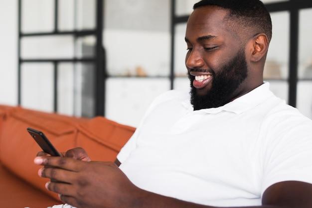 Hübscher erwachsener mann, der sein telefon durchsucht