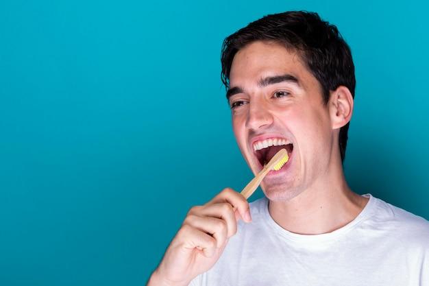 Hübscher erwachsener mann, der seine zähne putzt