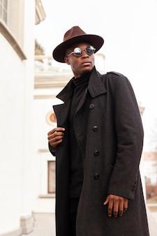 Hübscher erwachsener mann mit hut und sonnenbrille