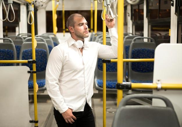 Hübscher erwachsener mann mit öffentlichen verkehrsmitteln