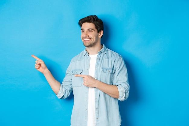 Hübscher erwachsener mann stellt produkt vor, schaut und zeigt mit den fingern nach links und fördert etwas vor blauem hintergrund
