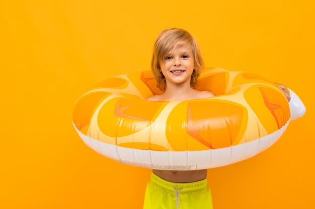 Hübscher europäischer blonder junge in gelben badehosen mit schwimmender kreisananas auf einem orangefarbenen hintergrund