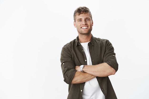 Hübscher europäischer männlicher typ mit weißem, perfektem lächeln, das die hände über den körper gekreuzt hält und zufrieden grinst, sich selbstbewusst und selbstzufrieden fühlt und erfreut gegen die weiße wand posiert