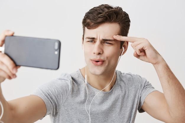 Hübscher europäischer mann mit stilvollem haarschnitt und blauen augen, die weiße kopfhörer tragen, handy halten, für selfie posieren, gesichter machen, hand hinter augenbraue halten. gesichtsausdrücke