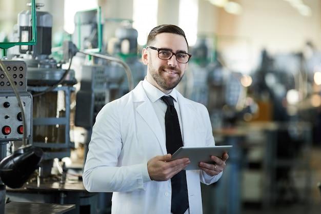 Hübscher fabrikmanager, der tablette hält