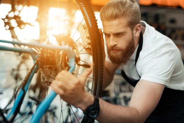 Hübscher fahrradmechaniker repair bicycle in der werkstatt