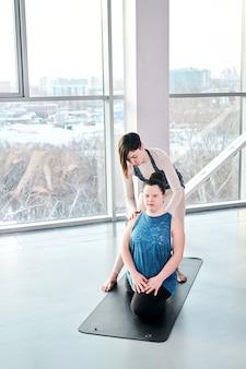 Hübscher fitnesstrainer in aktivkleidung, der sich über einen behinderten lernenden beugt, der auf einer matte sitzt, während er ihr bei einer der yogaübungen im fitnessstudio hilft