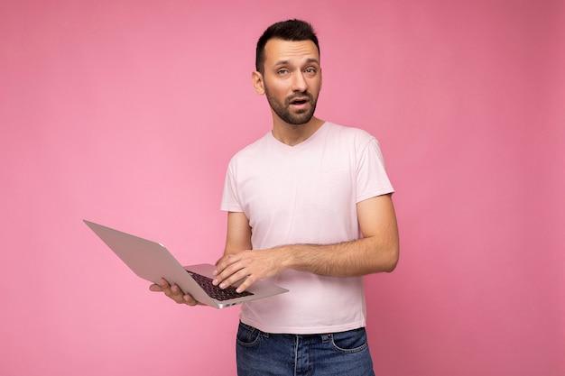 Hübscher fragender brunet-mann, der laptop-computer hält und hand zeigt, die kamera im t-shirt auf lokalisiertem rosa hintergrund betrachtet.