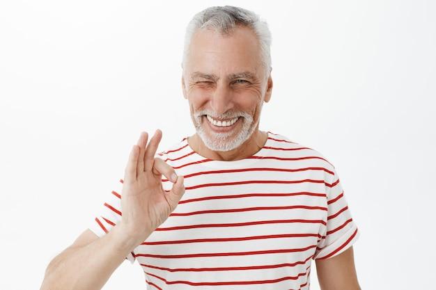 Hübscher frecher älterer mann versichern, zeigt gute geste und lächelt erfreut