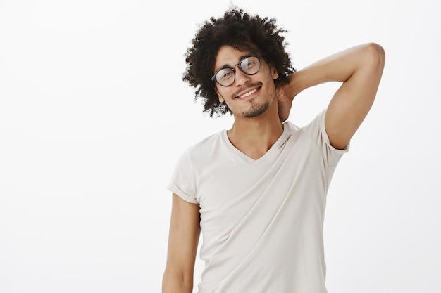 Hübscher frecher schwarzer mann in den gläsern, die erfreut lächeln