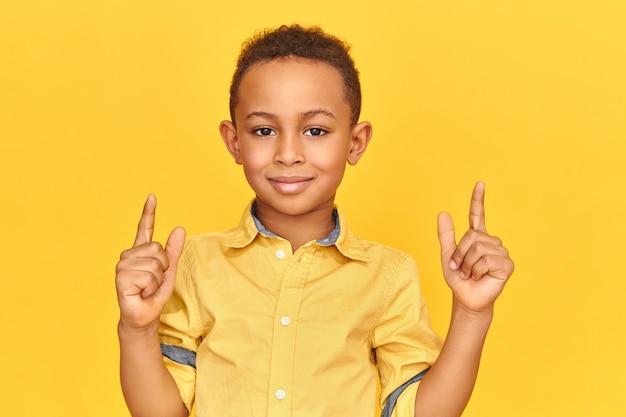 Hübscher freudiger afroamerikanischer junge, der glücklichen gesichtsausdruck hat, in die kamera lächelt, beide zeigefinger hebt und nach oben zeigt.