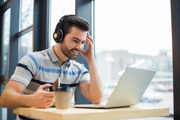 Hübscher freudiger glücklicher mann, der kopfhörer trägt und musik hört, während er den laptopbildschirm betrachtet