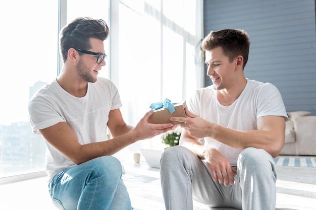 Hübscher freudiger mann, der lächelt und seinem männlichen partner ein geschenk präsentiert, während er neben ihm auf dem boden sitzt.