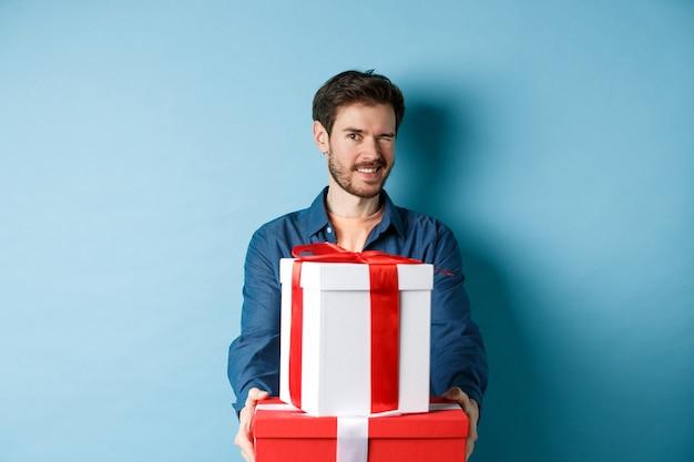 Hübscher freund, der in die kamera zwinkert und einen glücklichen valentinstag wünscht, hände mit geschenkboxen ausstreckend, romantische überraschung machend, über blauem hintergrund stehend.