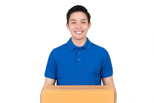 Hübscher freundlicher asiatischer lieferer im tragenden paketkasten des blauen polohemdes