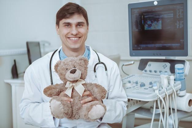 Hübscher freundlicher männlicher arzt, der plüsch-teddybärspielzeug hält und zur kamera lächelt