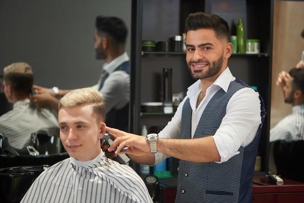Hübscher friseur, der den haarschnitt des kunden trimmt, kamera und das lächeln betrachtet.
