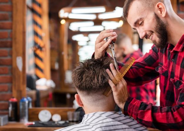 Hübscher friseur, der einen hippie-haarschnitt macht
