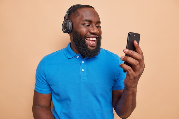 Hübscher fröhlicher bärtiger mann hört musik über kopfhörer hält handy macht videoanruf hat lustige online-gespräche in lässigen t-shirt-posen drinnen gekleidet
