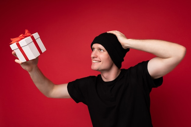 Hübscher, fröhlicher, fröhlicher lächelnder junger mann, isoliert über roter hintergrundwand, der einen schwarzen hut und ein schwarzes t-shirt trägt, das eine weiße geschenkbox mit rotem band hält und die gegenwart betrachtet und spaß hat