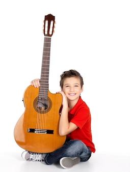 Hübscher fröhlicher junge mit der akustikgitarre