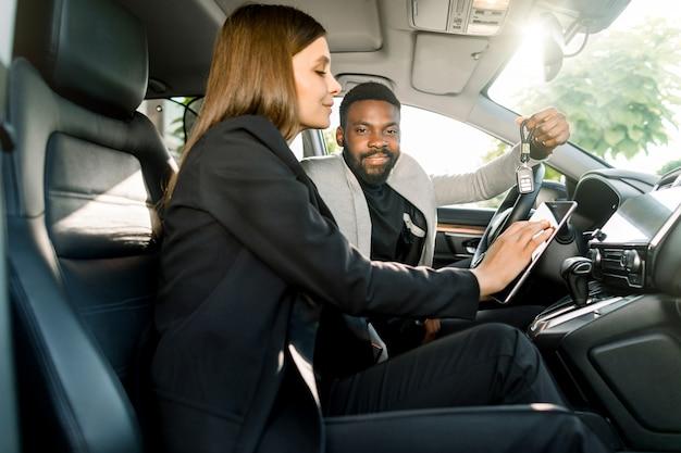 Hübscher fröhlicher junger afrikanischer mann, der autoschlüssel von seinem neuen luxusauto hält, während im auto zusammen mit hübschem frauenautoverkaufmanager sitzt, der eine tablette hält
