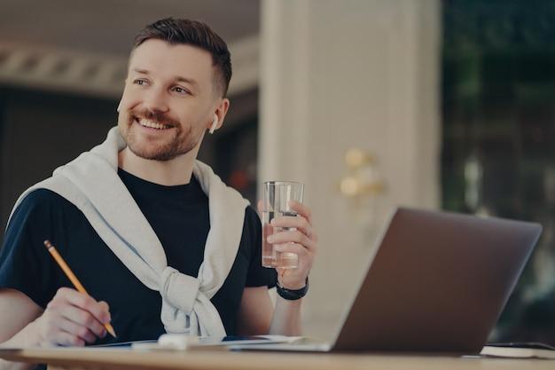 Hübscher fröhlicher junger männlicher freiberufler in freizeitkleidung, der sich glücklich fühlt, ein glas wasser und einen bleistift hält und mit positivem gesichtsausdruck beiseite schaut. lächelnder unternehmer, der im home office arbeitet