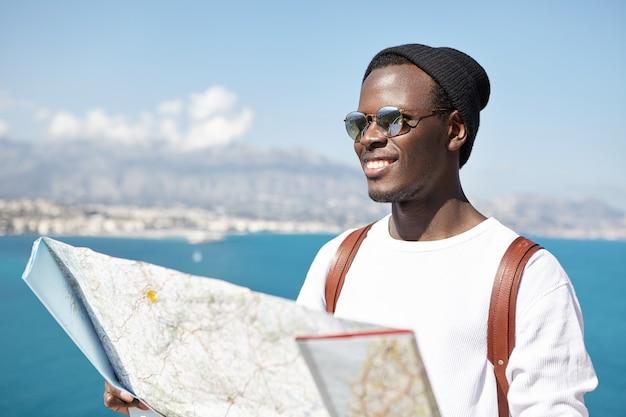 Hübscher fröhlicher junger männlicher tourist gekleidet in stilvoller kleidung, die glücklich lächelt