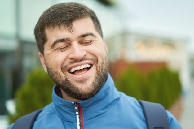 Hübscher fröhlicher kaukasischer tourist 30 jahre alt lacht, während er auf stadtstraße geht.