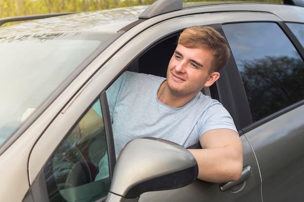 Hübscher fröhlicher kerl, fahrer, junger positiver mann, sein auto fahrend, lächelnd, ragen vom autofenster heraus. glücklicher käufer eines neuen autos, das das fahren genießt. emotion, glück, freude konzept
