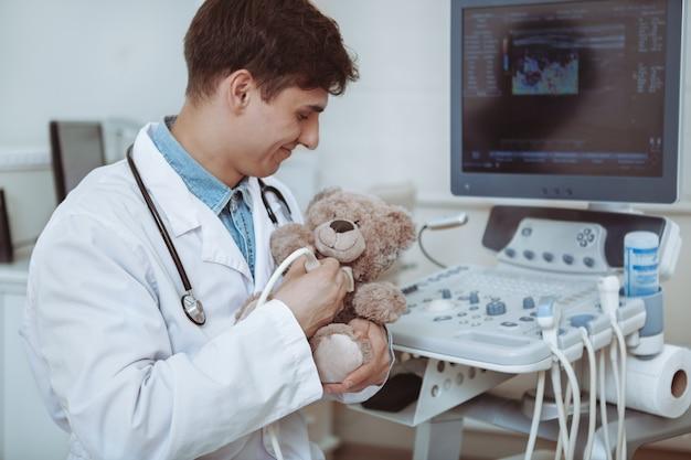 Hübscher fröhlicher männlicher arzt, der ultraschallscanner auf einem plüschtier teddybär verwendet