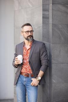 Hübscher fröhlicher mann, der nahe bürogebäude steht, das wegwerfbecher kaffee hält