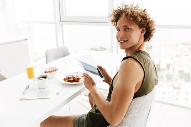Hübscher fröhlicher mann, der tablet-computer verwendet