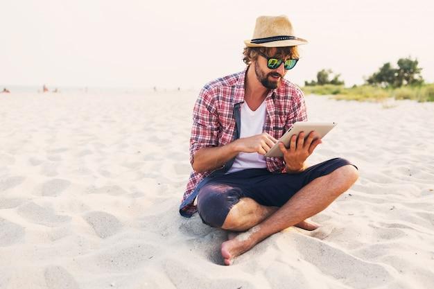 Hübscher fröhlicher mann mit bart im strohhut, kariertem hemd und stilvoller sonnenbrille, die auf weißem sand sitzt und tablette verwendet