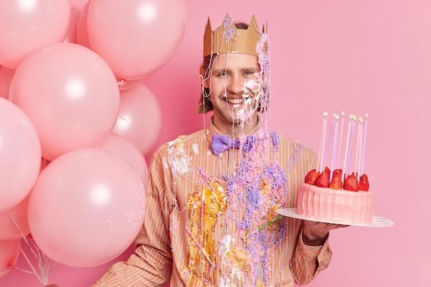 Hübscher fröhlicher mann steht schmutzig mit sahne hält köstlichen erdbeerkuchen feiert geburtstagsstände mit feiertagsattributen, die über rosa wand isoliert werden