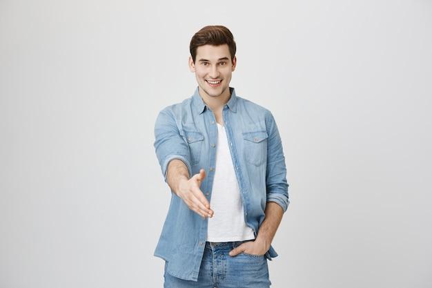 Hübscher fröhlicher mann streckt hand zum händedruck aus