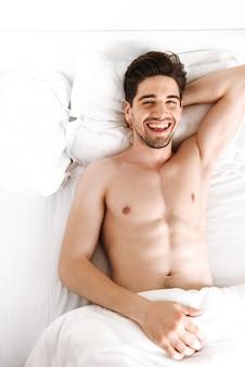 Hübscher fröhlicher nackter mann liegt im bett