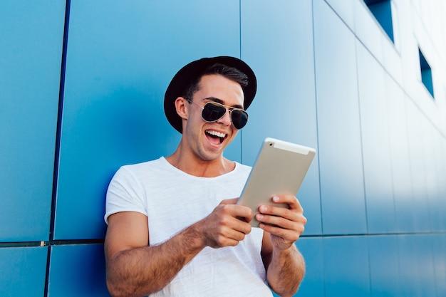Hübscher froher mann, der den tablettenschirm, nett lachend betrachtet und passt etwas auf.