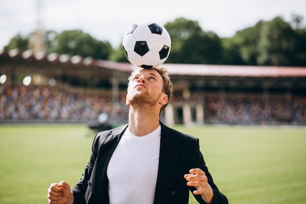 Hübscher fußballspieler am stadion im anzug