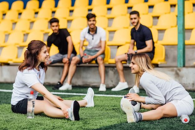 Hübscher fußballspieler, der die beinmuskulatur ausdehnt und sich auf das spiel im stadion vorbereitet