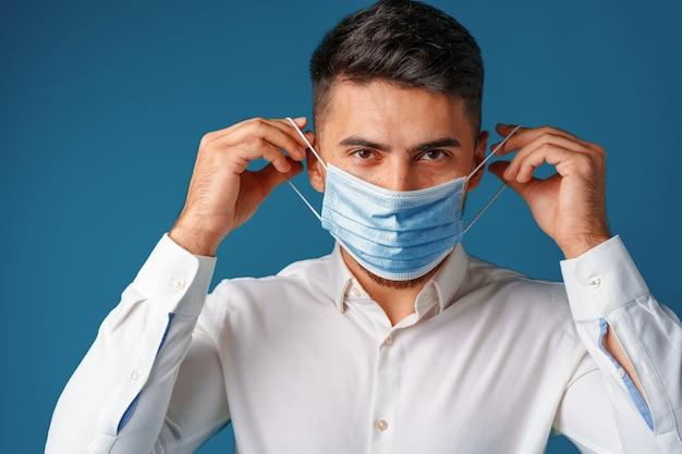 Hübscher gemischter rassenmann, der medizinische gesichtsmaske trägt