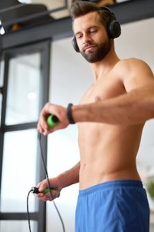 Hübscher gentleman, der springseil hält und den kalorienverbrauch auf dem aktivitätstracker überprüft, während er musik über drahtlose kopfhörer hört