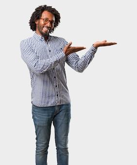 Hübscher geschäftsafroamerikanermann, der etwas mit den händen, ein produkt zeigend hält
