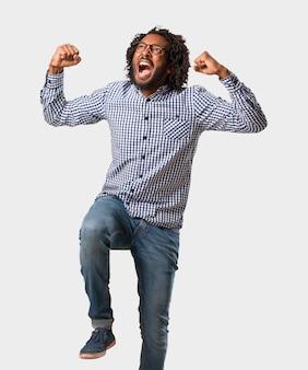 Hübscher geschäftsafroamerikanermann sehr glücklich und aufgeregt, arme anheben, einen sieg oder einen erfolg feiern und die lotterie gewinnen
