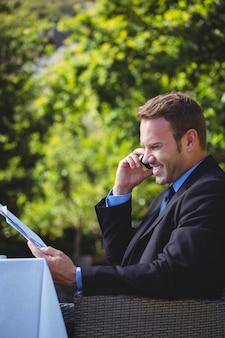 Hübscher geschäftsmann am telefon und lesen des menüs